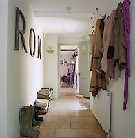 A jumble of coats on old-fashioned racks and a pile of logs stored in a heap on the stone-flagged floor create a welcoming and homely air in the entrance hall