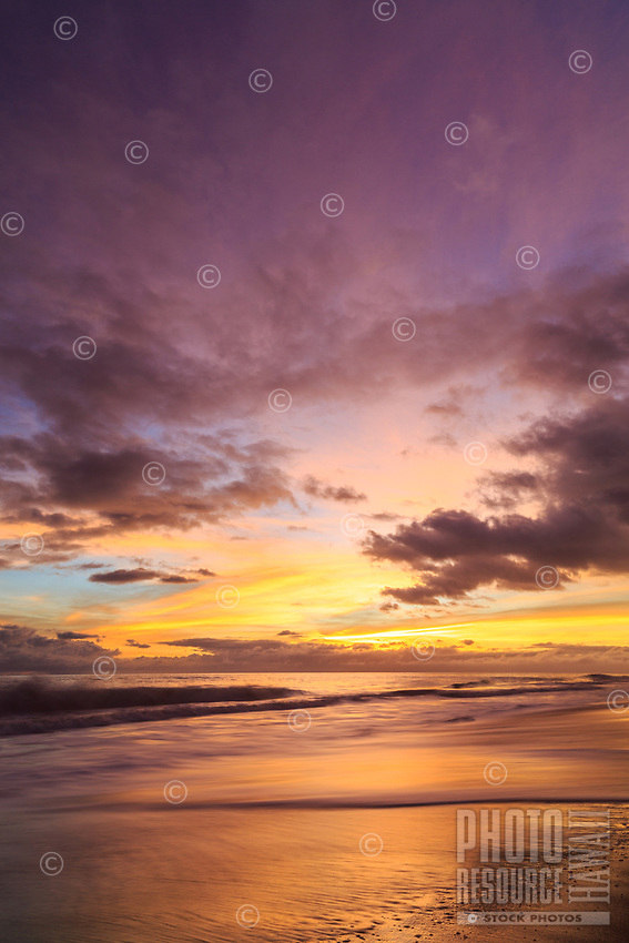 Purple and gold clouds fill the sky at sunset as the surf washes onto the sandy shores of Kekaha Beach, Kaua'i.