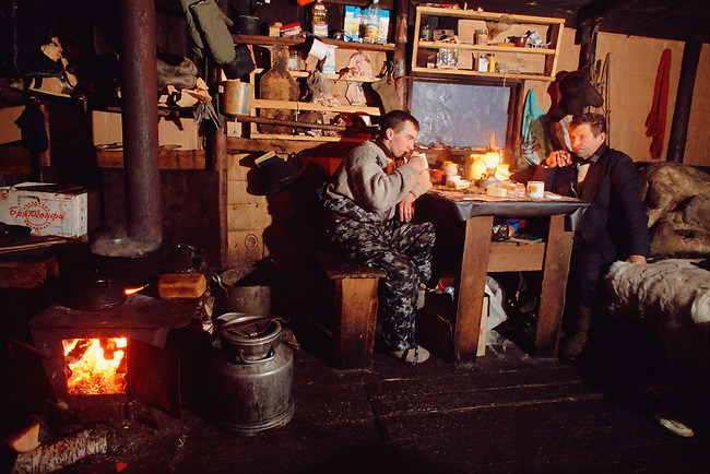 Two Sami reindeer herders relax in their hut after a days' work at their winter pastures. Lovozero, Murmansk, NW Russia.
