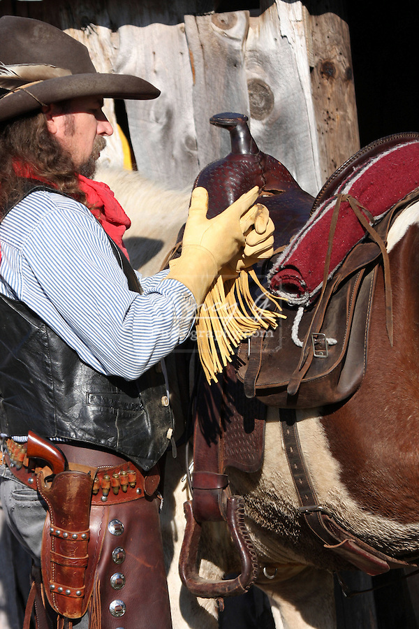 A cowboy taking off his leather gloves saddle fringe yellow