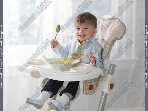 One and a half year old happy boy sitting in a high chair and eating soup with a spoon, spilling it on his shirt