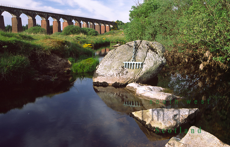 Art artist Matt Bakers Scene Shifter sculpture on the Big Water of Fleet burn with the old railway viaduct behind in Cairnsmore of Fleet National Nature Reserve in the Galloway Hills Scotland UK