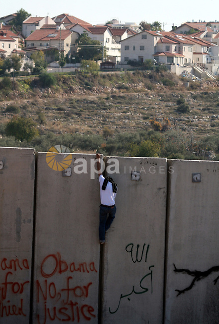 A masked Palestinian protestor climbs Israel's separation wall during a weekly demonstration against Israeli occupation in the West Bank village of Nilin, on December 02, 2011. Photo by Issam Rimawi