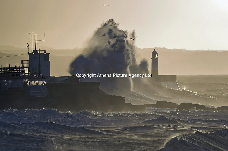 """Pictured: Waves crash into a lighthouse in Porthcawl, Wales, UK. Thursday 07 February 2019<br /> Re: Warnings of strong wind were in place across the whole of Wales starting Wednesday night.<br /> A yellow """"be aware"""" weather warning was issued from 10pm on Wednesday until 9am on Thursday.<br /> may be delayed on exposed routes."""