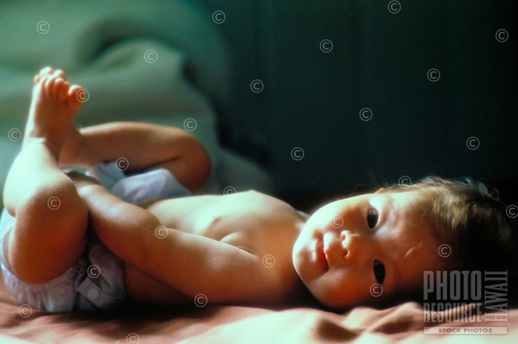 A cute six month old Japanese/Caucasian baby lying on his back looks deeply and peacefully at the camera lens.
