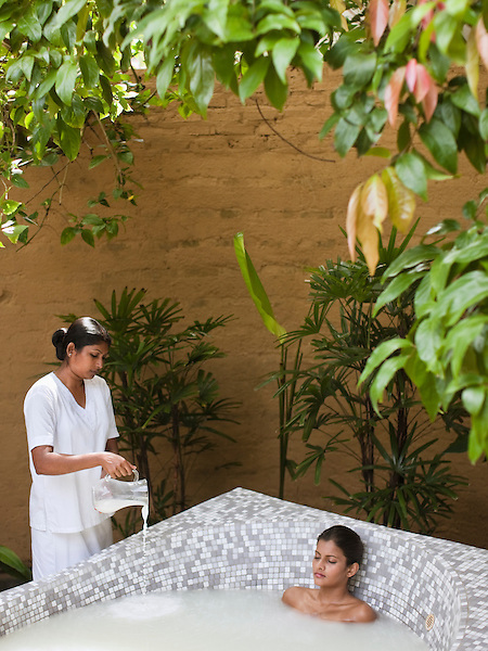 A woman soaks in a jacuzzi filled with milk to nourish and moisturize the skin at the Sahana Spa, Saman Villas, Aturuwella, Bentota, Sri Lanka. This Aromatic Milk Bath is the grand finale of a 135-minute spa treatment called the Sahana Coconut Skin Treat, which also involves a Hot Stone Massage, Aloe Honey Herb Wrap and Rose Gel Facial.