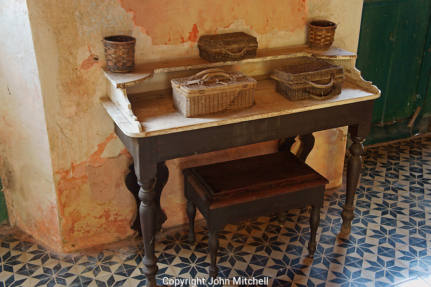 Colonial antique table covered with baskets in the main building at Hacienda Yaxcopoil, Yucatan, Mexico.