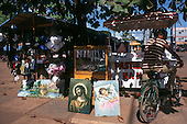 Belem, Brazil. Market stalls, one selling paintings of Jesus Christ and of a sleeping child, Amazon lanscapes, footballs, with a man on a bicycle.