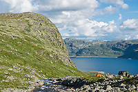 orange single person tent in mountains of Jotunheimen national park with lake Bygdin in background, Norway