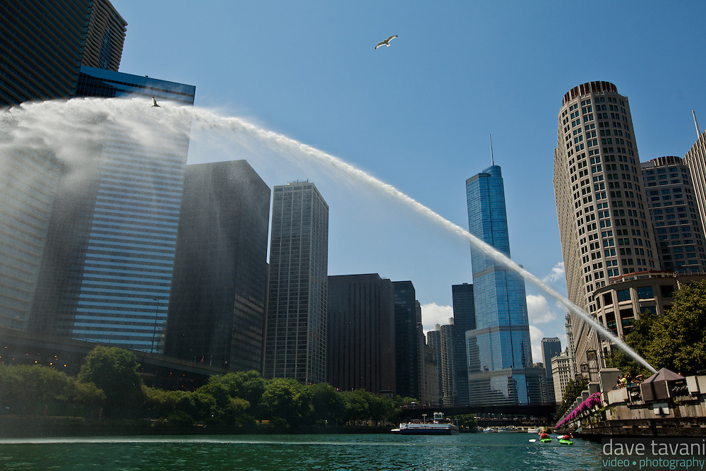 A sprinkler shoots water over the Chicago River while gulls fly overhead. This view of Chicago is from a kayak at river level.