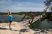 Young woman stretches atop the 360 Bridge, a famous tourist lookout in Lake Austin, Texas.