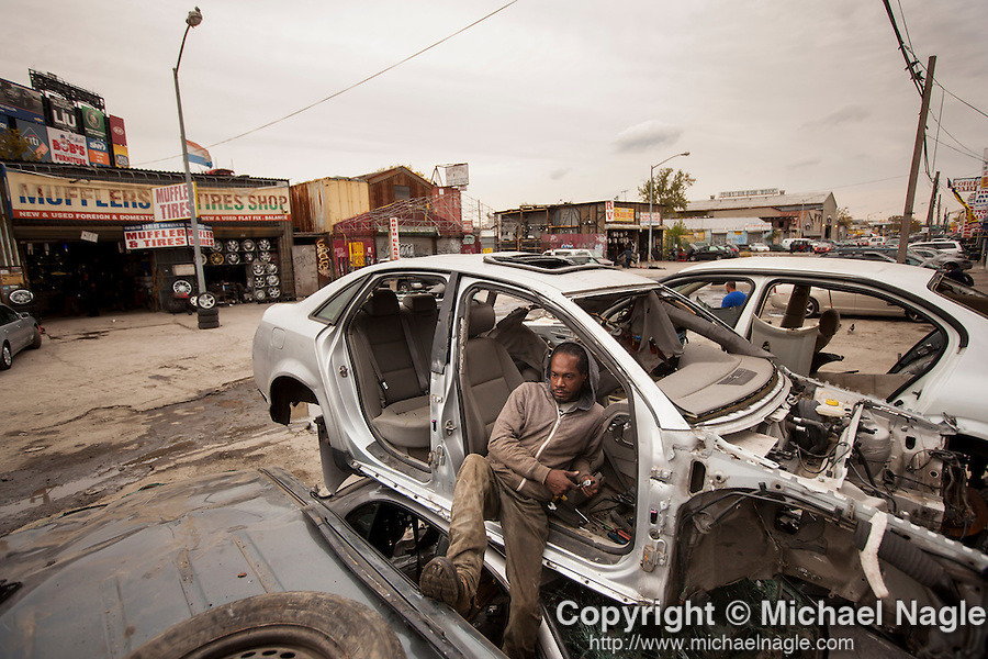 QUEENS, NY -- OCTOBER 22, 2013:  Kareem Williams sits in a scrapped car in front of ACDC Scrap Metal Inc. in Willets Point on October 22, 2013 in Queens.  Photographer: Michael Nagle for The New York Times