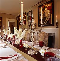 The dining table is laid for a festive occasion and the walls are covered in a fabric of thin red and white stripe with an abstract painting by Bianca Smith above the fireplace