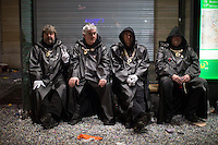 Members of a 'clique' dressed all in black, sit at a tram shelter in the old town of Basel near the end of Fasnacht, the Carnival of Basel, in Switzerland. Feb. 26, 2015.