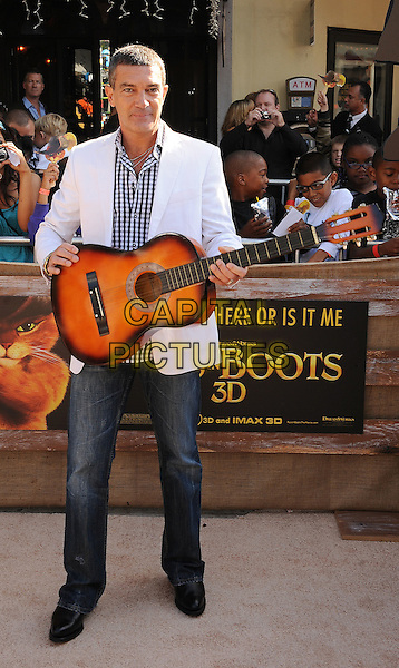 Antonio Banderas.The L.A. Premiere of 'Puss in Boots' held at The Regency Village Theatre in Westwood, California, USA..October 23rd, 2011.full length white suit jacket black check shirt  jeans denim guitar .CAP/ROT/TM.©Tony Michaels/Roth Stock/Capital Pictures