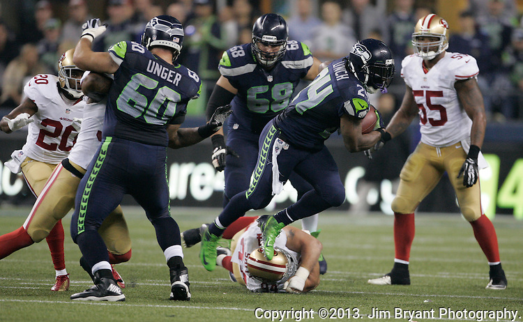 Seattle Seahawks  running back Marshawn Lynch (24) breaks a tackle by San Francisco 49ers  defensive tackle Justin Smith (94) in the third quarter at CenturyLink Field in Seattle, Washington on September 15, 2013.  Lynch finished with 135 total yards, including 98 yards rushing yards on 28 carries, scored three touchdowns in the Seattle Seahawks 29-3 win over the 49ers. ©2013. Jim Bryant Photo. ALL RIGHTS RESERVED.