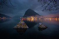"CHESwitzerland. Canton Ticino. Lugano. Night view on Monte San Salvatore and Lake Lugano from Park Ciani. Night fall. An exhibition ""Reflections of Light"" by artist Helicon Xhixha who is a contemporary albanian artist known for his stainless steel sculptures. Lake Lugano (Italian: Lago di Lugano or Ceresio) is a glacial lake. Parco Ciani is a green area of the city of Lugano, built in 1845, when the Ciani brothers bought the property. In 1912, it became property of the municipality of Lugano. It extends over an area of about 63,000 (mq). 17.03.2019 © 2019 Didier Ruef"