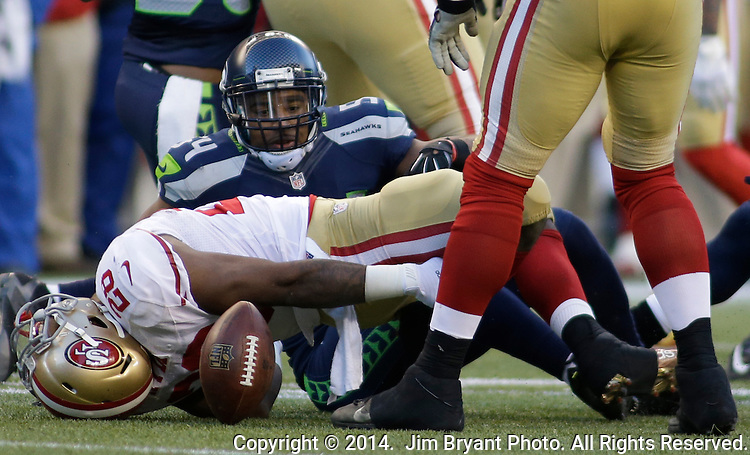 Seattle Seahawks  linebacker Bobby Wagner (54) eyes a loose ball after tackling San Francisco 49ers running back Carlos Hyde (28)  at CenturyLink Field in Seattle, Washington on December 14, 2014.  Hyde was running down by contact. The Seahawks beat the 49ers 17-7.    © 2014. Jim Bryant Photo. All Rights Reserved.