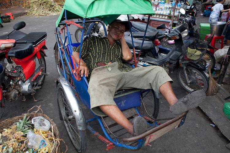 A sleeping cyclotaxi (rickshaw) driver in Phnom Penh, Cambodia. <br /> <br /> Photos &copy; Dennis Drenner 2013.