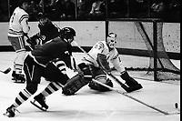 Seals vs Pittsburg Penguins 1975. Steve Durbano shoots on Seal goalie Gilles Meloche. Len Frig, in background (photo/Ron Riesterer)