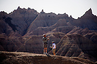 Tourists take pictures of the landscape in Badlands National Park in South Dakota, USA.