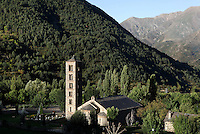 High angle view of Sant Climent de Taull church at sunrise against the massive slopes of the Pyrenees mountains, Taull, Province of Lleida, Catalonia, Spain. Consecrated by Ramon Guillem, the bishop of Roda in 1123, the church of Sant Climent is the largest; its characteristic Lombard architecture and interior decoration make it the symbol of Catalan Romanesque architecture. Its most imposing feature is its bell tower: it is square in plan and soars from a simulated solid base to six storeys. This is a church with three naves separated by cylindrical columns, topped by three semicircular apses. It is known for its campanile and for its murals, which were removed to the MNAC (National Art Museum of Catalonia, Barcelona) in 1922, to prevent the theft of the murals. The Catalan Romanesque churches of the Vall de Boí were declared a World Heritage Site by UNESCO in November 2000. Picture by Manuel Cohen.