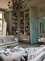A traditional sitting room decorated in grey blue. Books and other objects are displayed on shelving built into one corner of the room. Two sofas are placed either side of an ottoman.