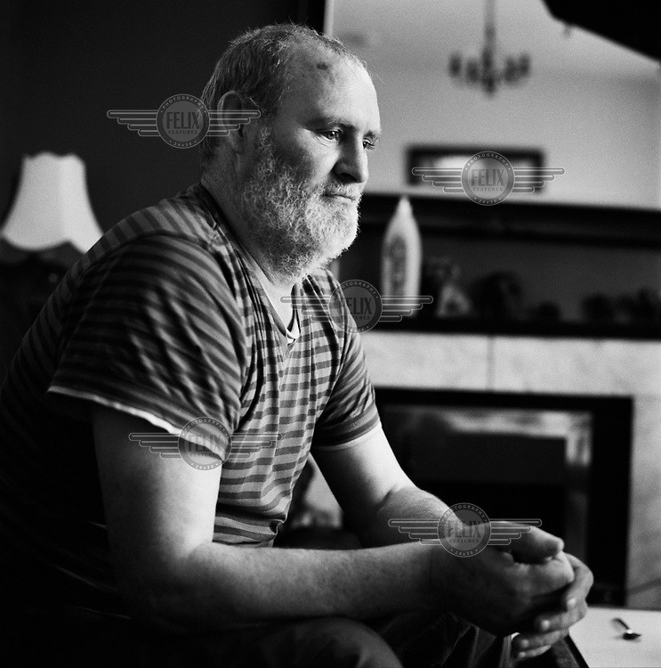 Brendan, a resident of the Fettercairn Estate, sitting in his living room.