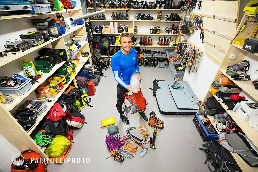 Ueli Steck in his home gear room packing climbing gear into a backpack for a climbing trip. Switzerland.