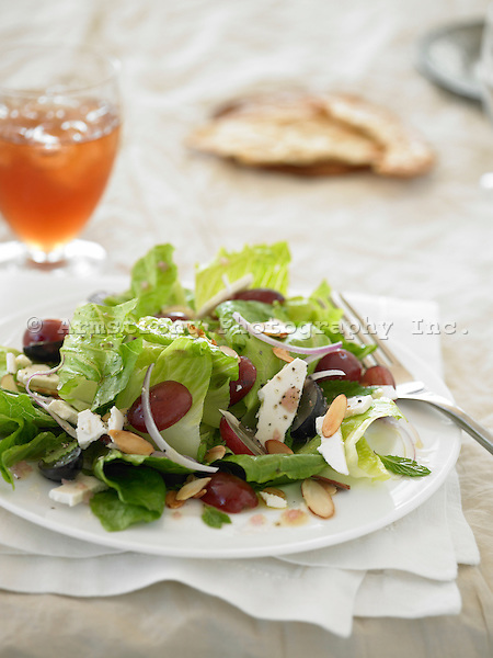 Salad with romaine lettuce, grapes, red onions, almonds, and cheese, with iced drink in background.
