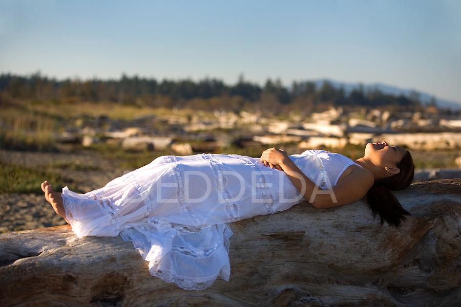 A young Filipino woman wearing a white dress on the beach.