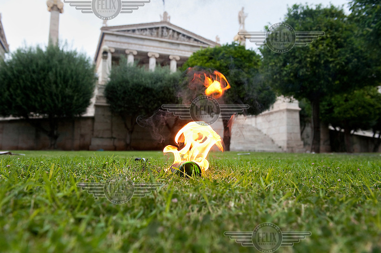 A petrol bomb on fire in the small park in front of the Academy of Athens during the the protests against the  unpopular austerity measures.