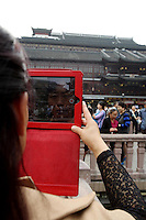 A woman uses her iPad to take pictures at the Yuyuan Garden.<br />