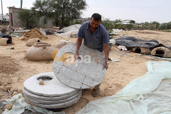A Palestinian man, Iyad Abu Samhadana, prepares the clay ovens to earn their living, in Rafah in the southern Gaza Strip, on November 27, 2016. Photo by Abed Rahim Khatib
