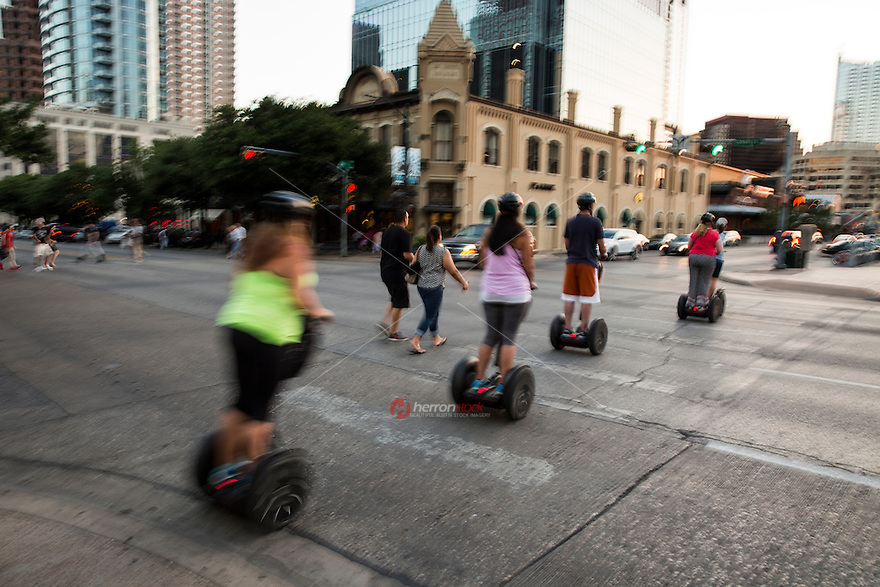 A Segway Tour group takes in sightseeing activities in downtown Austin, Texas. Segway is an electric scooter and popular mode of transport for navigating traffic and busy downtown Austin streets.