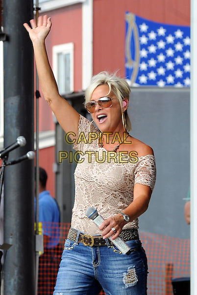 "LORRIE MORGAN  .on stage during her performance on opening day of ""Jamboree In The Hills 2010"" also known as the ""Super Bowl of Country Music"", Morristown, Ohio, USA, 15th July 2010..festival concert live gig half length  microphone jeans  beige lace off the shoulder top hand waving sunglasses arm raised up                      .CAP/ADM/JN.©Jason L Nelson/AdMedia/Capital Pictures."
