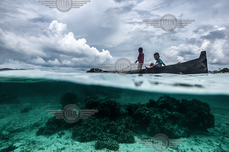 Two Bajau children pull in a fishing net from a small wooden canoe near Malenge island, Indonesia. Bajau children are taught to swim, dive and fish from an early age. (Photo: Aurélie Marrier d'Unienville)