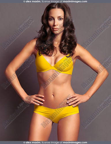 Young attractive woman wearing yellow underwear isolated on gray studio background