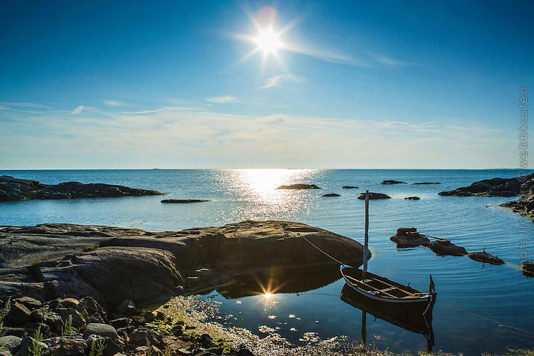Liten segelbåt i trä vid klippa vid havet och sol över horisonten vid Landsort Stockholms skärgården