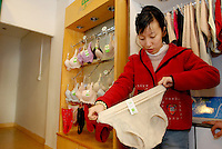 Liu Yanxiu tastes the elastic on a pair of underwear as she shops for new clothing to wear in the days following her wedding at a clothing store in Guangdong province, China on January 26, 2007.