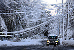 A vehicle drives down Franklin Street in Vernon going around the down wires, after the the record breaking snow storm brought down trees and utility wires leaving more than 700, 000 CL+P customers in the dark, Sunday, October 30, 2011. (Jim Michaud/Journal Inquirer).