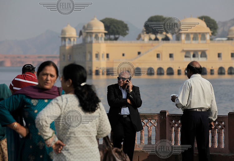 "People relax  near the Jal Mahal (meaning ""Water Palace""), a palace located in the middle of the Man Sagar Lake in Jaipur city, the capital of the state of Rajasthan, India. The palace and the lake around it were renovated and enlarged in the 18th century by Maharaja Jai Singh II of Amber...The urban lake gets filled up during the rainy season; over the years, once the reservoir became full during rainy season, it got covered with Hyacinth. During this period the red stoned palace became approachable only by boat and through a causeway, and presented a spectacle on the way to Jaipur city from Delhi."