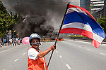 14 MAY 2010 - BANGKOK, THAILAND: An anti-government protester waves the Thai flag in front of a burning barricade on Rama IV Rd Friday afternoon. Thai troops and anti government protesters clashed on Rama IV Road Friday afternoon in a series of running battles. Troops fired into the air and at protesters after protesters attacked the troops with rocket and small homemade explosives. Unlike similar confrontations in Bangkok, these protesters were not Red Shirts. Most of the protesters were residents of nearby Khlong Toei slum area, Bangkok's largest slum area. The running battle went on for at least two hours.   PHOTO BY JACK KURTZ