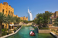 An abra, a water taxi, ferries passengers around the Madinat Jumeirah with the Burj al Arab Hotel, an icon of Dubai built in the shape of the sail of a dhow, and the Mina a?Salam Hotel in the background.    Dubai. United Arab Emirates.