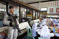 Heavily armed police guards a public school in the outskirts of the Pattani province. The situation changed dramatically for the pepole when the militants started targeting the children. Thailand is struggling to keep up appearances as the land of smiles has to face up to its troubled south. Since 2004 more than 3500 people have been killed and 4000 wounded in a war we never hear about. In the early hours of January 4th 2004 more than 50 armed men stormed a army weapons depot in Narathiwat taking assault rifles, machine guns, rocket launchers, pistols, rocket-propelled grenades and other ammunition. Arsonists simultaneously attacked 20 schools and three police posts elsewhere in Narathiwat. The raid marked the start of the deadliest period of armed conflict in the century-long insurgency. Despite some 30,000 Thai troops being deployed in the region, the shootings, grenade attacks and car bombings happen almost daily, with 90 per cent of those killed being civilians. 24.09.07. Photo: Christopher Olssøn