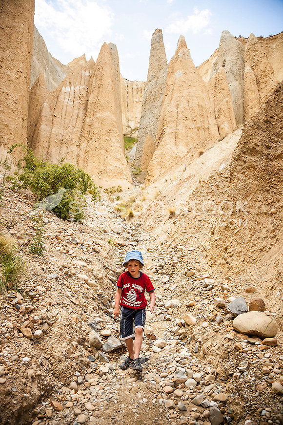 Boy (6 years) exploring the Clay Cliffs near Omarama, Canterbury, New Zealand - stock photo, canvas, fine art print