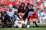 Ryan Finley (15) of the North Carolina State Wolfpack is sacked by D.J. Wonnum (8) of the South Carolina Gamecocks during second half action in the Belk College Kickoff at Bank of America Stadium on September 2, 2017 in Charlotte, North Carolina.  The Gamecocks defeated the Wolfpack 35-28.  (Brian Westerholt/Four Seam Images)
