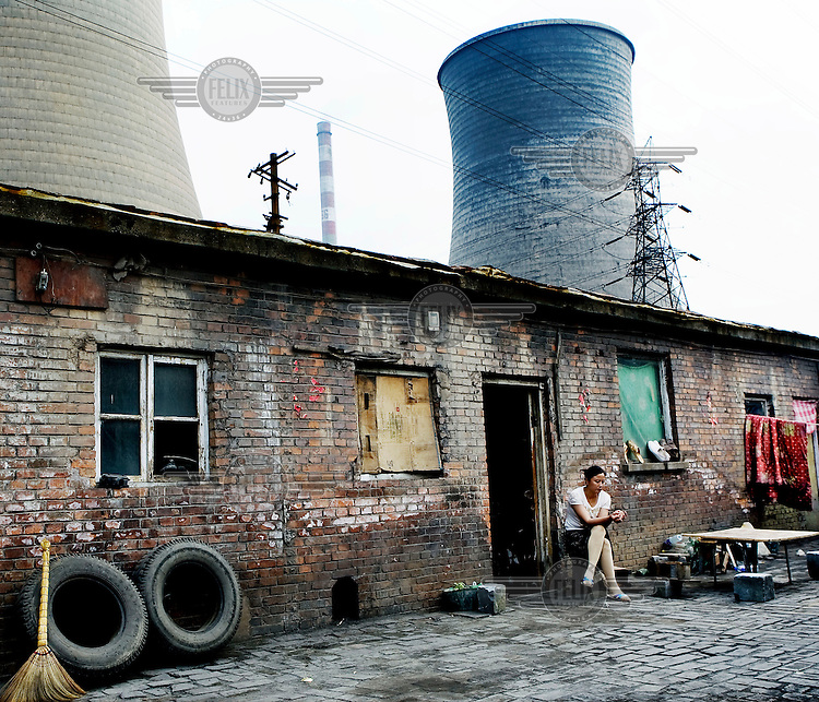 A woman sits outside her house at an industrial site where her family work.