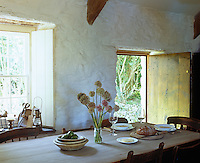 The whitewashed kitchen is dominated by a scrubbed wooden refectory table