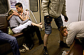Youngsters kiss and collapse on the metro in Moscow, Russia. .Picture by Justin Jin.